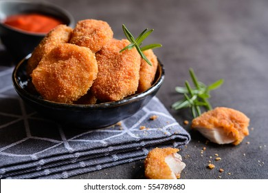Fried breaded chicken nuggets with tomato sauce