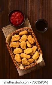Fried breaded crispy chicken nuggets in basket, ketchup and soft drink on the side, photographed overhead on dark wood with natural light