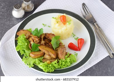 Fried bull testicles with cream and herbs served with mashed potato on a white plate on an abstract background. Healthy food concept.