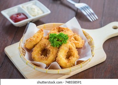 Fried calamari rings in wicker basket and sauce