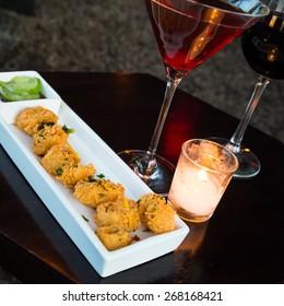 Fried calamari tapas with cocktail and candlelight