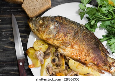 Fried carp with baked potatoes and mushrooms on a wooden background in rustic style. Fried fish.