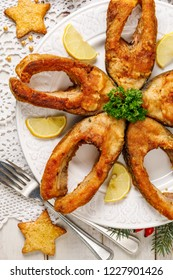Fried carp fish slices on a white plate, top view. Traditional christmas eve dish. Polish Christmas food