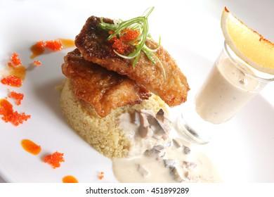 Fried CARP with garnish and mushroom sauce on plate