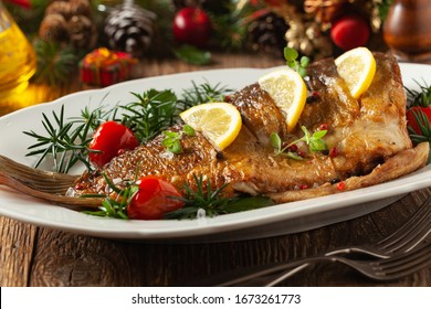 Fried carp whole. Served with lemon and cherry tomatoes on white plate. Christmas decoration.