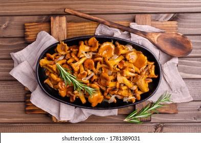 Champignons de girolles frits avec oignons et romarin sur fond bois foncé. Mise au point sélective.