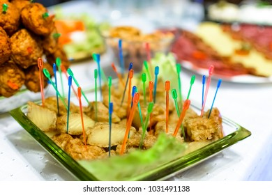fried cheese Kashkaval with toothpick in a green plate