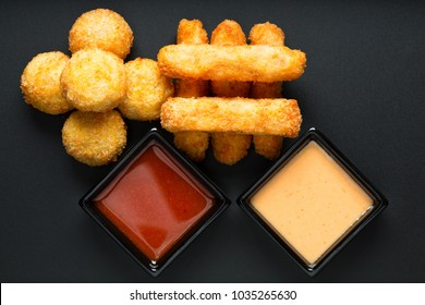 Fried cheese sticks and meat ball snack served with a sauce, top view on a black background