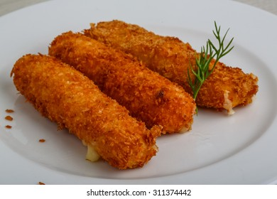Fried cheese sticks in pan with dill