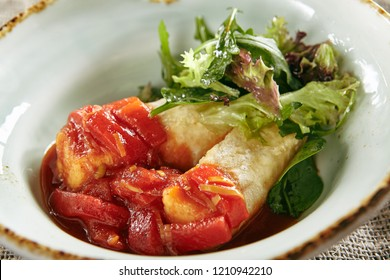 Fried Cheese, Sweet Pepper, Green Leaves of Lettuce and Arugula in Tomato Sauce Close Up. Capsicum Peppers or Bell Peppers with Baked Edam or Gouda Topped with Leaf Salad in Round Plate