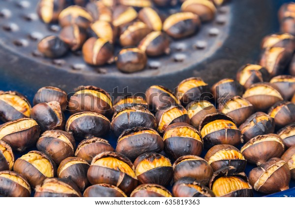 Fried chestnuts on the street. Street food. Roasted chestnuts served in a special perforated chestnut pan.