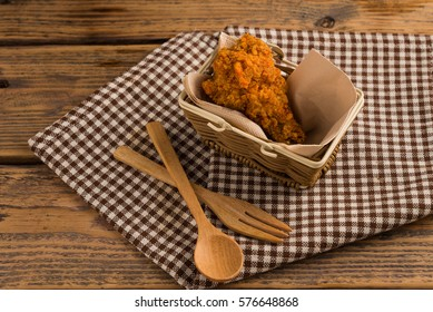 Fried chicken in basket on  wood table with black background.