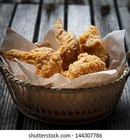 Fried Chicken in a basket on a wooden floor.