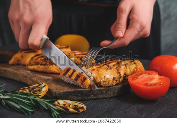 fried chicken breast on the board cut with a knife and fork. next to tomato, bell pepper and lemon with herbs and spices