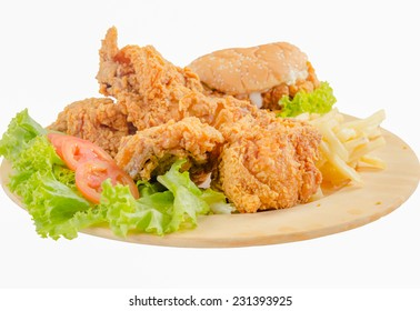 Fried chicken and burger with French Fries on wooden plate