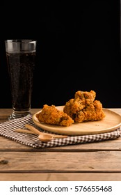 Fried chicken and cola on  wood with black background.