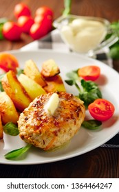Fried chicken cutlet with potato slices served with tomato cherry and corn salad. Traditional belorussian food - roasted minced meat and potato