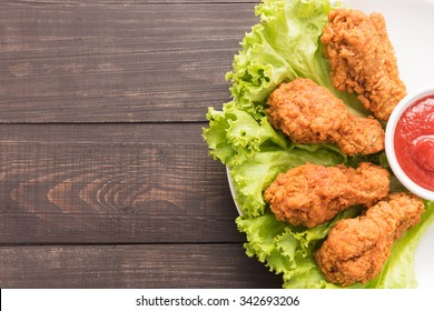 Fried chicken drumstick and ketchup on wooden background.