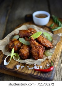 Fried chicken drumstick with spices and sauce on paper on a wooden board, old wooden background