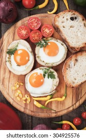 Fried chicken eggs in roasted potato shells served on wooden board