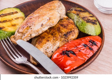 Fried chicken fillet with grilled vegetables in a plate on a rustic wooden table - close-up