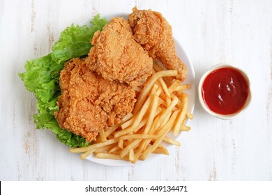 fried chicken and french fries on a wooden background