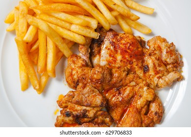 fried chicken with fries on white plate.
