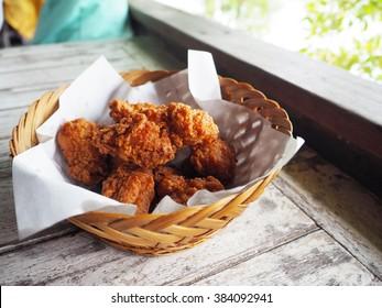 Fried chicken, karaage in basket on wood table beside river.