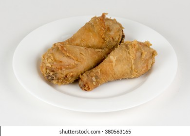 Fried chicken leg in breadcrumbs on white plate closeup isolated on white