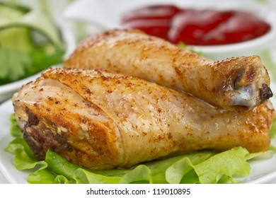 Fried chicken legs with cucumber salad and sauce close-up