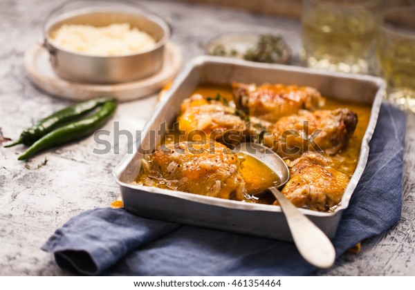Fried chicken legs meat in oven sheet with onion caramelized sauce and couscous bowl. Rustic style.