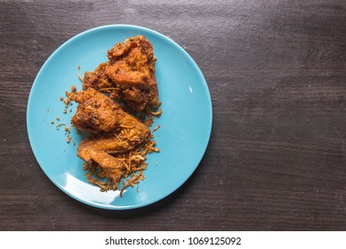 Fried chicken in the light blue dish on dark brown wooden.fried chicken the most famous food of Hat-yai Songkhla Thailand.that tourist want to eat.