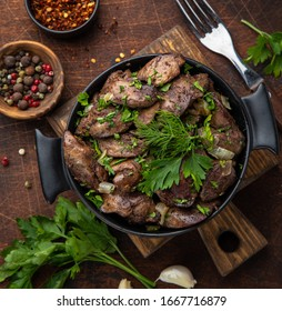 fried chicken liver in black pot, wooden background, top view, square image