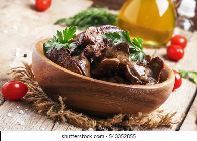 Fried chicken livers in a bowl, vintage wooden background, selective focus