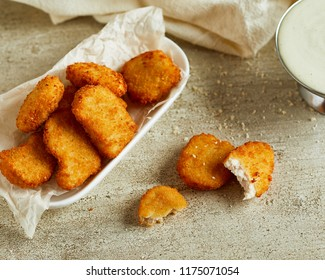 Fried chicken nuggets served on white plate. Fast food