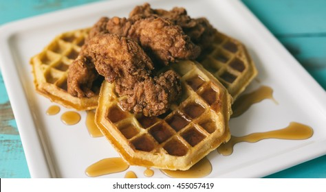 Fried chicken on top of three waffles with syrup. Shown on a white square plate.