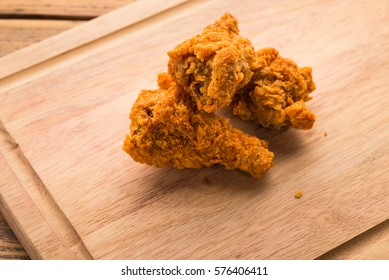 Fried chicken on  wooden cutting board.