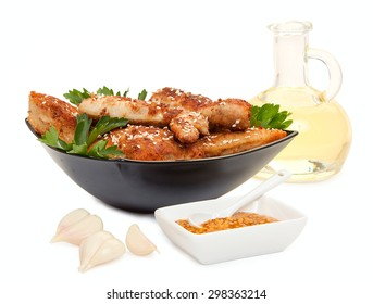 Fried chicken pieces coated with breadcrumbs with with parsley on a black plate, garlic, a bottle of vegetable oil, plate of mustard. Isolated on white background.