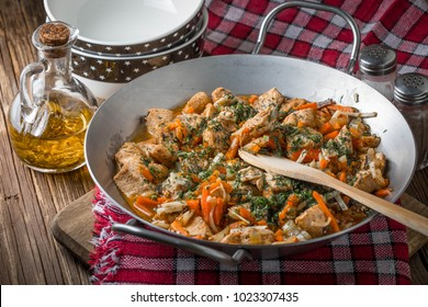 Fried chicken pieces with vegetables on a metal frying pan. Small depth of focus.