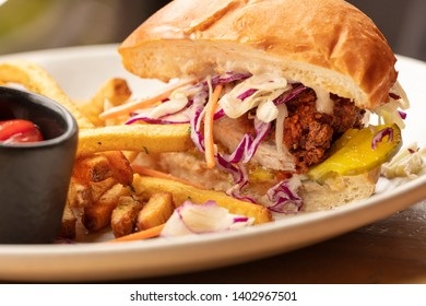 Fried chicken sandwich on a burger bun, garnished with slaw and a pickle,  and a side of french fries and ketchup
