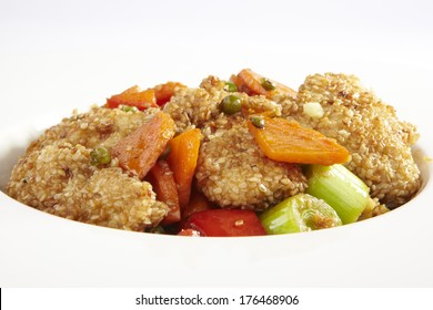 fried chicken with sesame and vegetables on a white plate
