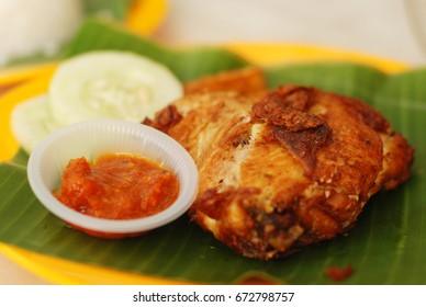 Fried chicken smashed with the pestle against mortar to make it softer also known as Ayam Penyet, an east Javanese dish, served with tomato hot paste and sliced cucumber.