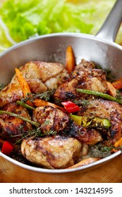 fried chicken with spices and vegetables on pan