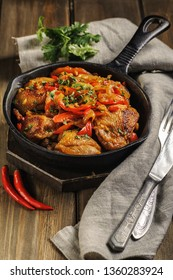 Fried chicken in spicy sauce with vegetables. Cooked in a cast iron pan. The pan is on a dark wooden background. Next is a natural linen napkin. Vertical.