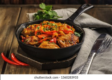 Fried chicken in spicy sauce with vegetables. Cooked in a cast iron pan. The pan is on a dark wooden background. Next is a natural linen napkin.