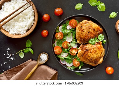 Fried chicken thighs with vegetables in plate and bowl of rice over black stone background. Top view, flat lay