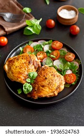 Fried chicken thighs with vegetables in plate on dark background