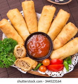 Fried chicken and vegetables spring rolls with red ketchup sauce