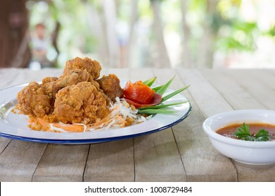 Fried chicken wing stick with coating flour in white dish and sweet chicken sauce on brown wooden table in green garden   /  Blurred and  Selective focus and space for message