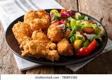 Fried chicken wings in breadcrumbs and fresh vegetable salad close-up on a plate. horizontal